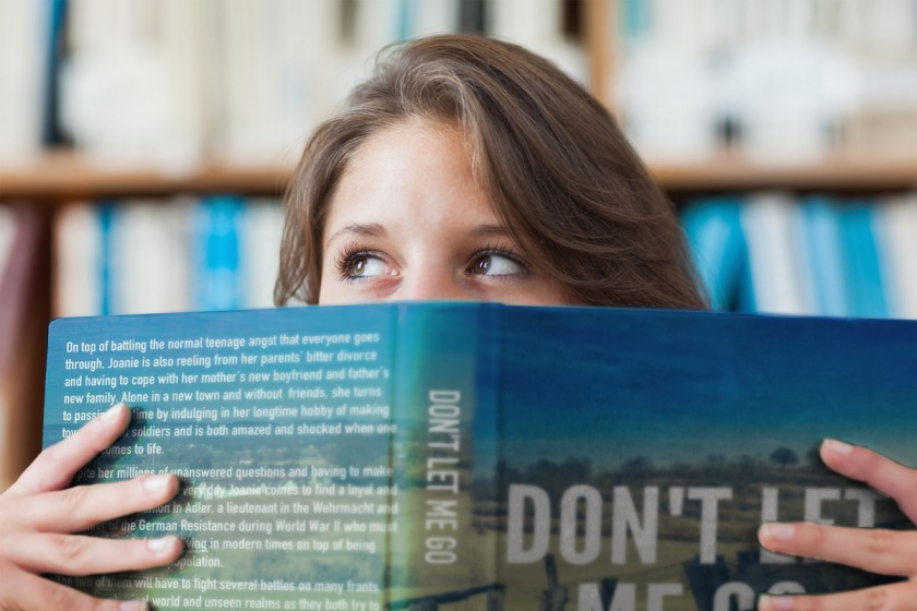 Close-up portrait of a female student holding book in front of her face in the library